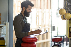 Salesman writing on clipboard at counter. In grocery shop Royalty Free Stock Images