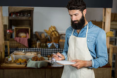 Salesman writing on clipboard at counter. In grocery shop Royalty Free Stock Photos