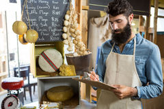 Salesman writing on clipboard at counter in grocery shop. In market Royalty Free Stock Photography