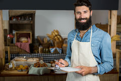 Salesman writing on clipboard at counter in grocery shop. Portrait of salesman writing on clipboard at counter in grocery shop Royalty Free Stock Images