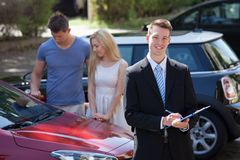 Salesman writing on clipboard with couple looking at car. Young salesman writing on clipboard with couple looking at new car in background royalty free stock photography