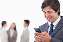 Salesman writing text message with team behind him Stock Image