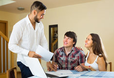 Salesman and young couple at home Stock Photography