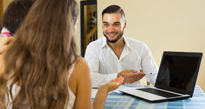 Salesman and young couple at home Stock Image