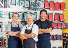 Salesmen Standing Arms Crossed In Hardware Shop Royalty Free Stock Photo