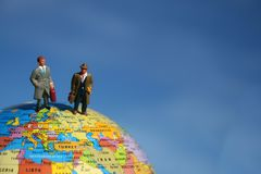 Salesmen standing on globe Royalty Free Stock Image