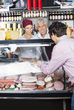 Salespeople Assisting Male Customer In Buying Cheese. At shop Royalty Free Stock Photo