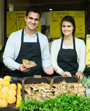 Salespeople with farm mushrooms in market, prices are on Spanish Royalty Free Stock Image