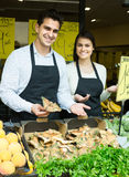 Salespeople with farm mushrooms in market, prices are on Spanish Stock Images