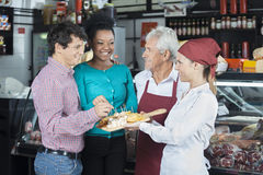 Salespeople Offering Cheese Samples To Customers In Shop. Happy salespeople offering free cheese samples to customers in shop Royalty Free Stock Photography