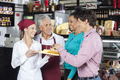 Salespeople Offering Cheese Samples To Customers In Shop. Happy salespeople offering free samples to customers in cheese shopr Stock Images