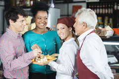 Salespeople Offering Cheese Samples To Customers In Supermarket. Happy salespeople offering free cheese samples to customers in supermarket Royalty Free Stock Image