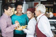 Salespeople som erbjuder ostprövkopior till kunder i supermarket royaltyfri bild
