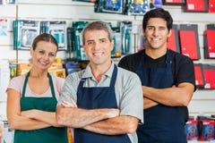 Salespeople som står armar som korsas i maskinvara, shoppar royaltyfri bild