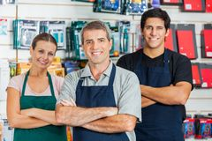 Salespeople Standing Arms Crossed In Hardware Shop. Portrait of smiling salespeople standing arms crossed in hardware shop Royalty Free Stock Image