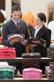 Salesperson Assisting Businessman. In clothes store stock photography