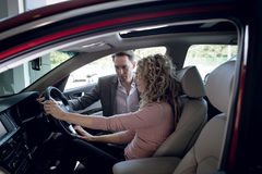 Salesperson assisting woman sitting in car. Salesperson assisting women sitting in car at showroom royalty free stock photography