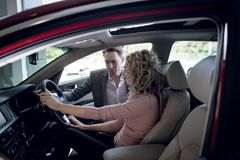 Salesperson assisting woman sitting in car. Salesperson assisting women sitting in car at showroom stock image