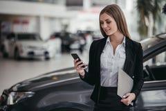 Salesperson at car dealership. Professional female salesperson at car dealership royalty free stock photos