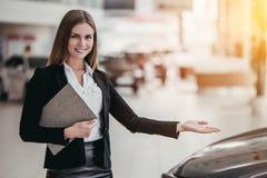 Salesperson at car dealership. Professional female salesperson at car dealership stock image