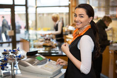 Salesperson at cash register. Saleswoman working at cash register in shop Royalty Free Stock Photo