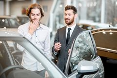 Salesperson with client in the car showroom. Car salesman helping a young ashamed client to make a decision showing intrerior of a luxury car at the showroom royalty free stock photo