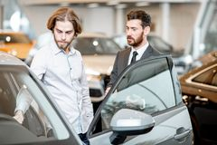Salesperson with client in the car showroom. Car salesman helping a young male client to make a decision showing intrerior of a luxury car at the showroom royalty free stock photos