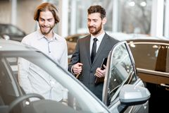 Salesperson with client in the car showroom. Car salesman helping a young male client to make a decision showing intrerior of a luxury car at the showroom royalty free stock image