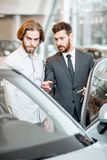 Salesperson with client in the car showroom. Car salesman helping a young male client to make a decision showing intrerior of a luxury car at the showroom stock image