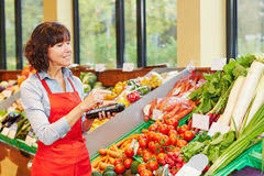 Salesperson counting vegetables for delivery. Salesperson counting vegetables with mobile data registration terminal for a new delivery in a supermarket royalty free stock photos