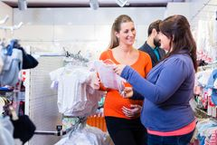 Salesperson with couple buying baby clothes in shop Royalty Free Stock Images