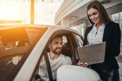 Salesperson with customer in car dealership. Professional salesperson during work with customer at car dealership stock photography