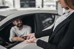Salesperson with customer in car dealership stock image