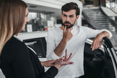 Salesperson with customer in car dealership. Professional salesperson during work with customer at car dealership. Naming all the benefits of new vehicle royalty free stock photography