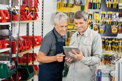 Salesperson And Customer Using Tablet Computer. In hardware store Royalty Free Stock Photography
