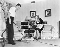 Salesperson demonstrates a vacuum cleaner to a housewife in her home royalty free stock image