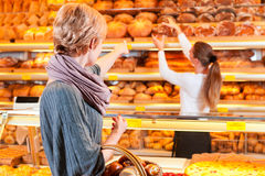 Salesperson with female customer in bakery. Female baker or saleswoman in her bakery with a female customer and fresh pastries or bakery products Royalty Free Stock Photography