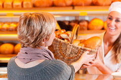 Salesperson with female customer in bakery. Female baker or saleswoman in her bakery with a female customer and fresh pastries or bakery products stock image