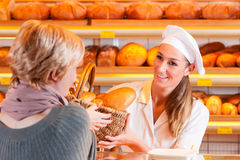 Salesperson with female customer in bakery. Female baker or saleswoman in her bakery with a female customer and fresh pastries or bakery products Stock Images
