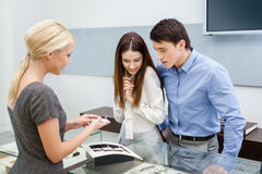 Salesperson helps couple to choose jewelry Royalty Free Stock Images