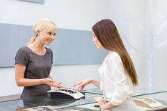 Salesperson helps lady to choose jewelry. At jeweler's shop. Concept of wealth and luxurious life stock photos