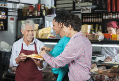 Salesperson Offering Samples To Customers In Cheese Shop. Happy male salesperson offering free samples to customers in cheese shop Royalty Free Stock Images