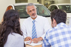 Salesperson pointing something on booklet. At new car showroom royalty free stock photography