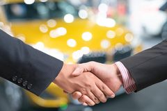 Salesperson selling cars at car dealership. 1 royalty free stock photography