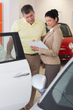 Salesperson showing clipboard to sign to customer. At new car showroom royalty free stock photography