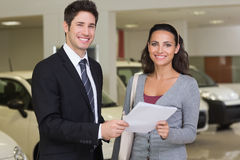 Salesperson showing clipboard to sign to customer Stock Photography