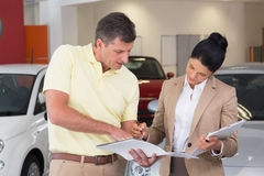 Salesperson talking with her customer while holding a booket Royalty Free Stock Images