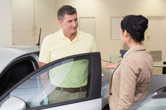 Salesperson talking with her customer. At new car showroom stock images