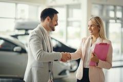 Salesperson workin at car dealership. Salesperson selling cars at car dealership royalty free stock images