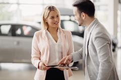 Salesperson workin at car dealership. Salesperson selling cars at car dealership royalty free stock photo